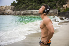 Handsome muscular young man on the beach with headphones Stock Photography