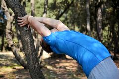 Handsome muscular young man is doing stretching exercises in forest. Sportsman wearing sportswear in landscape nature outdoor. Pretty guy, active, cross fit Stock Images