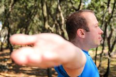 Handsome muscular young man is doing stretching exercises in forest. Sportsman wearing sportswear in landscape nature outdoor. Pretty guy, active, cross fit Royalty Free Stock Photo