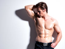 Handsome muscular young man looking sideways. Handsome muscular young man looking sideways posing at studio on a white background with contrast shadows stock photos