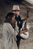 Handsome musician man with guitar and cowboy hat hug with sensua Royalty Free Stock Photography