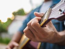 Handsome musician playing acoustic guitar on blur background. mu stock photos