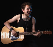 Handsome musician playing guitar. On black background Royalty Free Stock Photo
