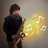 Handsome musician playing on saxophone with musical notes. Handsome young musician playing on saxophone with musical notes Royalty Free Stock Photography