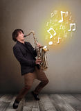 Handsome musician playing on saxophone with musical notes Stock Photography