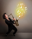 Handsome musician playing on saxophone with musical notes Stock Image