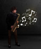 Handsome musician playing on saxophone with musical notes. Handsome young musician playing on saxophone with musical notes Stock Image
