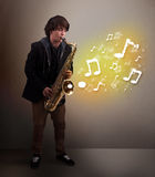 Handsome musician playing on saxophone with musical notes. Handsome young musician playing on saxophone with musical notes Stock Images
