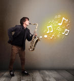 Handsome musician playing on saxophone with musical notes Stock Photo