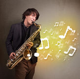 Handsome musician playing on saxophone with musical notes Royalty Free Stock Image