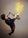 Handsome musician playing on saxophone with musical notes Stock Images