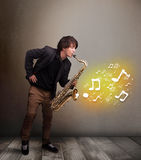 Handsome musician playing on saxophone with musical notes. Handsome young musician playing on saxophone with musical notes Royalty Free Stock Photo