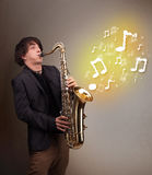 Handsome musician playing on saxophone with musical notes Stock Photos