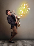 Handsome musician playing on saxophone with musical notes. Handsome young musician playing on saxophone with musical notes Royalty Free Stock Image