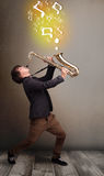 Handsome musician playing on saxophone with musical notes. Handsome young musician playing on saxophone with musical notes Royalty Free Stock Photos