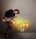 Handsome musician playing on saxophone. Handsome young musician playing on saxophone with musical notes Royalty Free Stock Photography