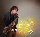 Handsome musician playing on saxophone. Handsome young musician playing on saxophone with musical notes Stock Photo