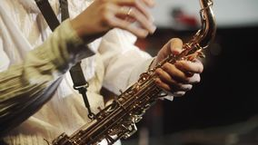 Handsome musician plays jazz at saxophone in gig stock footage