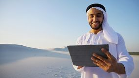 Successful Arabian businessman holds in hands and uses tablet, s royalty free stock photo
