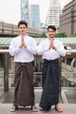 Handsome Myanmar men welcome hand sign. Portrait of Handsome Burmese or Myanmar men with longyi traditional dress perform salute or pay respect hand sign in Royalty Free Stock Photo