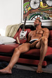 Handsome naked atletic man bodybuilder with electric guitar play Royalty Free Stock Photography
