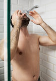 Handsome naked young man taking shower in bathroom.  Stock Photos