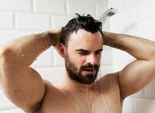 Handsome naked young man taking shower in bathroom.  Stock Photo