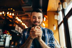 Handsome natural man looking at the camera and drinking tea Royalty Free Stock Image