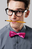 Nerd. Handsome nerd biting yellow pencil royalty free stock photography