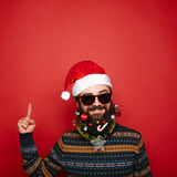 Handsome new year man with decorated beard pointing up Royalty Free Stock Photography