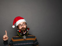 Handsome new year man with decorated beard pointing upwards Stock Image
