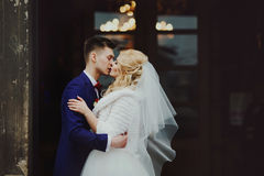 Handsome newlywed groom kissing happy bride outside church after Royalty Free Stock Photo