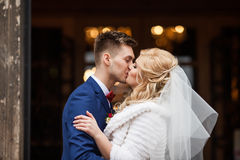 Handsome newlywed groom kissing happy bride outside church after Stock Photos