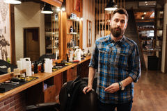 Handsome nice barber standing near his workplace. Ready to work. Handsome positive nice barber standing near his workplace and holding scissors while being ready Royalty Free Stock Images