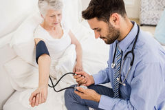 Handsome nurse checking blood pressure of elderly woman Royalty Free Stock Photos