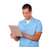 Handsome nurse guy using his tablet pc Royalty Free Stock Photography
