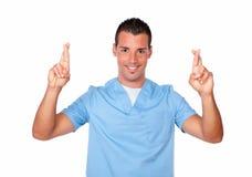 Handsome nurse man crossing his fingers Stock Photos