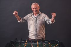 Happy old man. Handsome old man in casual clothes is playing table football, looking at camera and smiling, on gray background royalty free stock image