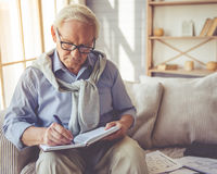 Handsome old man at home. Handsome old man in eyeglasses is writing in his notebook while sitting on couch at home Royalty Free Stock Photo