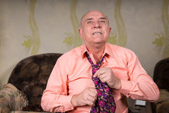 Handsome old man intently putting on his tie. Close up handsome old man intently putting on his tie sitting in his room Royalty Free Stock Images