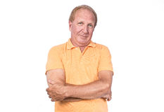 Handsome old man with orange polo-shirt hands crossed Royalty Free Stock Photography