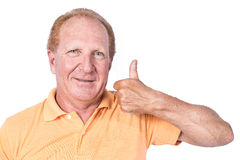 Handsome old man with orange polo-shirt shows thumb up stock photography