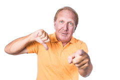 Handsome old man with orange polo-shirt shows thumb up and pointin royalty free stock images