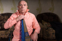 Handsome old man trying on several ties. Handsome senior sad man is trying on a beautiful tie sitting in his living room wearing a stylish shirt and some ties on Stock Images