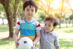 Handsome older brother holding ball and ready for playing in the park with younger brother. Little boy is always accompanied with royalty free stock photo