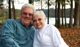 Handsome older couple. A handsome man embraces his pretty wife by a lake in the evening stock photography