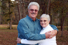 Handsome older couple. A handsome man embraces his pretty wife in the forest stock photos