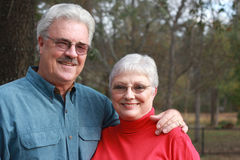Handsome older couple. A handsome man embraces his pretty wife in the forest royalty free stock images