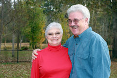 Handsome older couple. A handsome man embraces his pretty wife in the forest royalty free stock photo