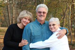 Handsome older couple with daughter. Elderly couple embrace each other while their daughter joins in stock images